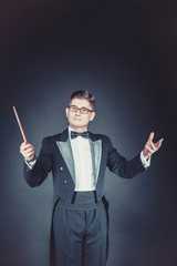 young man in a tuxedo conducting