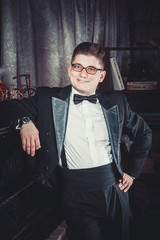 a man in a tuxedo and glasses looking at the camera and smiling