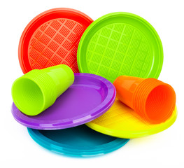 Disposable bright plastic plates and cups on white background