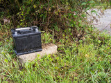 Dumped used car battery. Rubbish disposal, environment problem.
