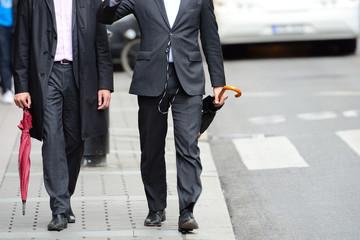 Anynomus men walking talking on sidewalk