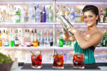 Beautiful brunette barmaid make cocktails