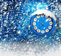 Snow-covered clock on abstract blue background