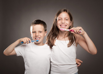 children brushing her teeth on a gray background