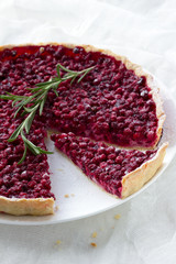 Tart with red bilberry on a white plate