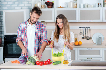 Cooking together. Young and beautiful couple in love looking at