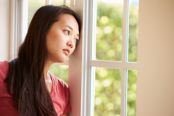 Thoughtful Asian Woman Looking Out Of Window
