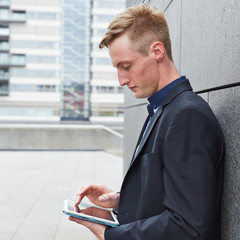 Mann arbeitet mit Tablet Computer unterwegs