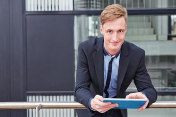 Geschäftsmann steht draußen mit Tablet PC