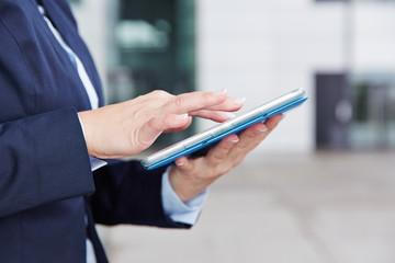 Hand einer Geschäftsfrau auf Tablet Computer