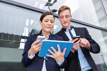 Frau und Mann vergleichen Smartphone und Tablet Computer