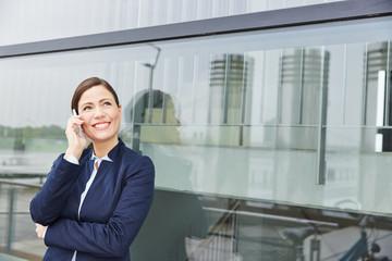 Geschäftsfrau vor Büro in der Stadt mit Smartphone