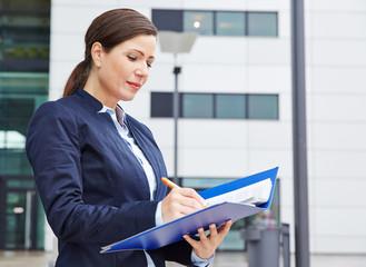 Geschäftsfrau liest Vertrag im Freien