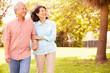 Senior Asian Couple Walking Through Park Together - 70642560