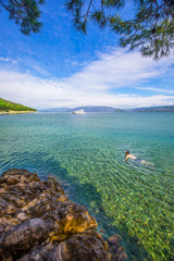 Young man swimming in stone beach with crystal clear tourquise s