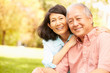 Leinwanddruck Bild - Portrait Of Senior Asian Couple Sitting In Park Together