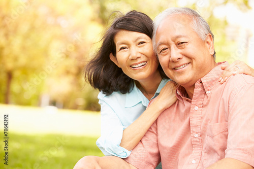 Leinwanddruck Bild Portrait Of Senior Asian Couple Sitting In Park Together