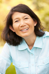 Portrait Of Senior Asian Woman Sitting In Park