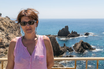 portrait of woman with sunglasses on the coast