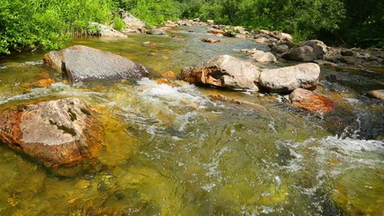 mountain river flowing over rocks in summer - slider dolly shot