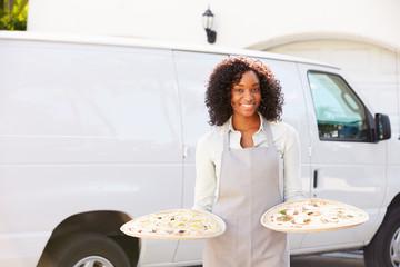 Woman Delivering Pizza Standing In Front Of Van