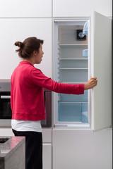 Terrified woman against the empty fridge