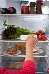 Woman choosing food from refrigerator