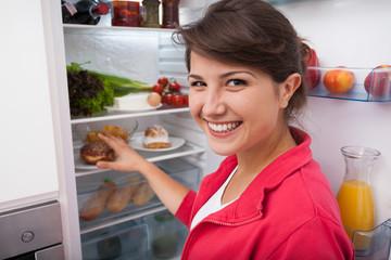 Woman taking doughnut from fridge