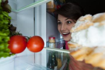 Happy girl looking into the fridge
