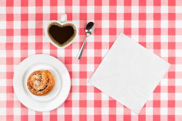 Cinnamon bun and heart-shaped mug with napkin