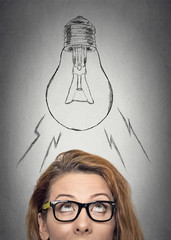 Woman with glasses having an idea looking up light bulb