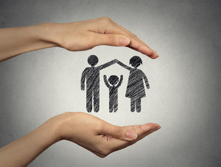 woman's hands protecting happy family, grey wall background