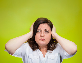 stressed woman covering ears looking up green background