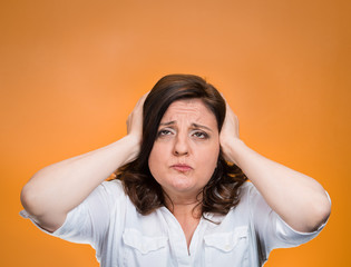 stressed woman covering ears looking up, orange background