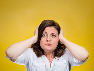 unhappy stressed woman covering ears looking up loud noise