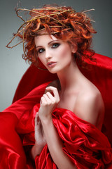 Beautiful girl in red fabric in a chaplet from branches.