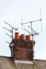 Red bricks chimney and TV antennas
