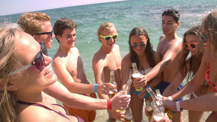 Group of friends cheers with beers at the beach in slow motion