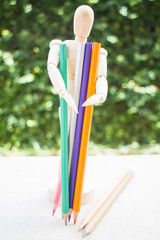 Wooden manikin and colour pencil on artist work table