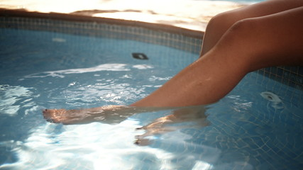 Woman's legs in water at poolside