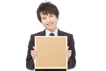メッセージボードを持って笑うビジネスマン