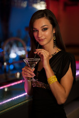Girl drinks a cocktail in night club