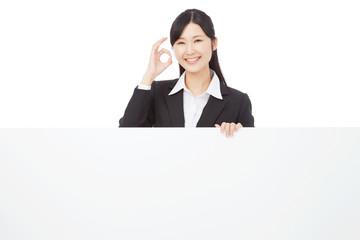 メッセージボードとOKサインするビジネスウーマン