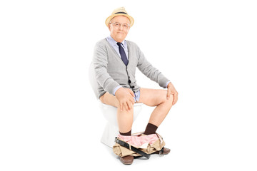 Studio shot of a happy senior seated on a toilet