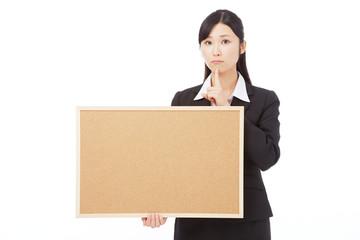 メッセージボードを持って考えるビジネスウーマン