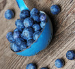 a ladle with blueberries on a table