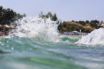 Splash water of Aegean Sea on the background of beach.