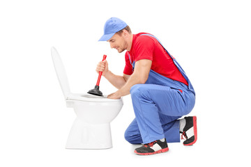 Male plumber working on a toilet with plunger