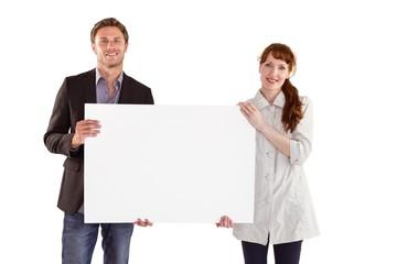 Smiling couple holding large sign