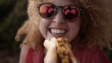 Girl biting into hotdog close to camera